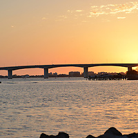 John Ringling Causeway Bridge and Golden Gate Point silhouetted against a golden sunset view from Bayfront Park, downtown Sarasota, Florida. recently named a great waterfront to visit by USA Today