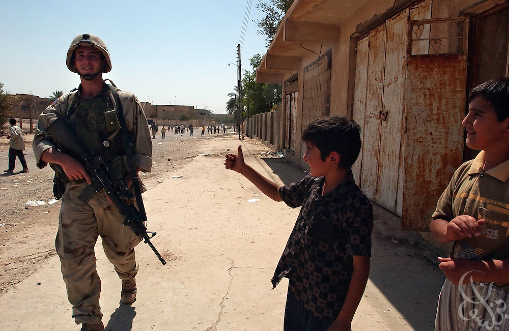 U.S. Army 4th Infantry Division, 1st Battallion, 12th regiment PFC John Stockstell from Palm Springs, CA gets the thumbs up sign of support from a local Iraqi boy as his squad conducts a daylight presence patrol August 24, 2003 through Samarra, Iraq.