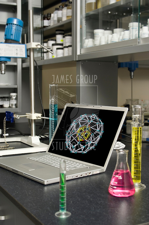 Laptop in a chemical laboratory amidst laboratory glassware and equipment