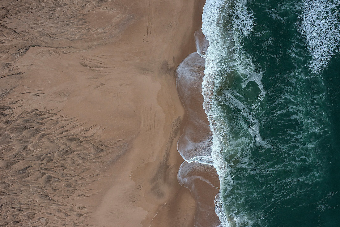 The Atlantic Ocean comes ashore kissing the Skeleton Coast of Namibia on August 11, 2015. The Skeleton Coast is located in northern Namibia and has long been a graveyard for unwary ships and their crews, hence its forbidding name. Early Portuguese sailors called it As Areias do Inferno (The Sands of Hell), as once a ship washed ashore, the fate of the crew was sealed. — © /Jeremy Lock