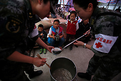Chinese medical officers ladle out dumplings as children looks on in a makeshift hospital in Taiping town of Lushan County, Sichuan Province, China, 23 April 2013. The Lushan Earthquake in Sichuan Province on 20 April 2013 resulted in 186 people dead, 21 missing, 11248 injured. About 1.72 million people were affected by the quake, while an initial estimate by the International Red Cross on Saturday put the number needing emergency shelter, water and food at 120,000. The China Earthquake Administration (CEA) recorded a magnitude 7.0 earthquake, while the US Geological Survey said it had measured 6.9.