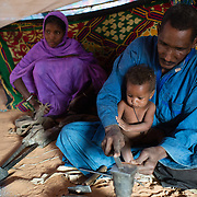 A man makes simple knives for sale from scrap metal while his son sits in his lap at the Mbera camp for Malian refugees in Mauritania on 2 March 2013.