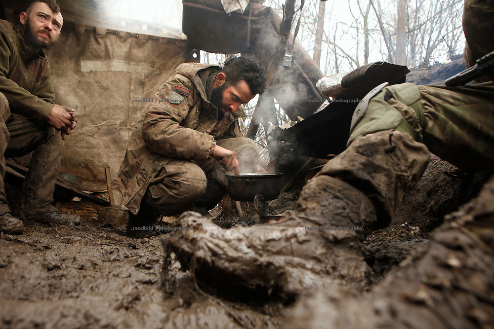 Ben (ce.) and Alex (le.) prepare a meal at the camp fire in the muddy trench at the donetsk frontline.<br /> <br /> Fascinated by war and convinced of a simple shaped nationalistic ideology, five vonuteer warriors from Europe and USA left behind their former lifes. Walking into battle in Ukraine, Ben, Alex, Craig, Charlie and Cowboy made it to the frontline and joint the right-wing militia Right Sector, supporting the ukrainian army which is short of staff. Receiving no payments but shelter, food and ammo the foreigners selfmade battlegroup Task Force Pluto is a loose union of individuals and no particular ukrainian phenomenon. The Boom Stick Brotherhood would move on to another conflict around the globe when Ukraine become boring to them. They want to be involved in battle. That&acute;s what they are aiming for. Living a dream of smoking guns, camaraderie and outdoor life. An extreme lifestyle devoted to an everyday look into the face of death.<br /> <br /> The Boom Stick Brotherhood is a multi-national, multi-religious and multi-ethnic group:<br /> Ben, an austrian infantryman travelling hot zones since years. Bored by his own reluctant national army at home he made plenty of experience in Kosovo, Syria, Iraq and Ukraine.<br /> Alex, Ben&acute;s brother in arms from austrian army times deserted and fled the country to get ultimately involed in frontline fights.<br /> Craig was fighting almost 6 years for the US-Army in Iraq and Afghanistan but got in conflict with the law afterwards. He escaped conviction by going abroad.<br /> Charlie was totally bored by his californian routine in Silicon Valley but failed to join the US-Army and French Foreign Legion. Eventually he found battle opportunities in Ukraine.<br /> Petty crook Cowboy got in trouble with US law only days before his Army unit was to deployed to Afghanistan. Later during a day release he made it from prison to France but French Foreign Legion rejected him. He gave Ukraine a go.
