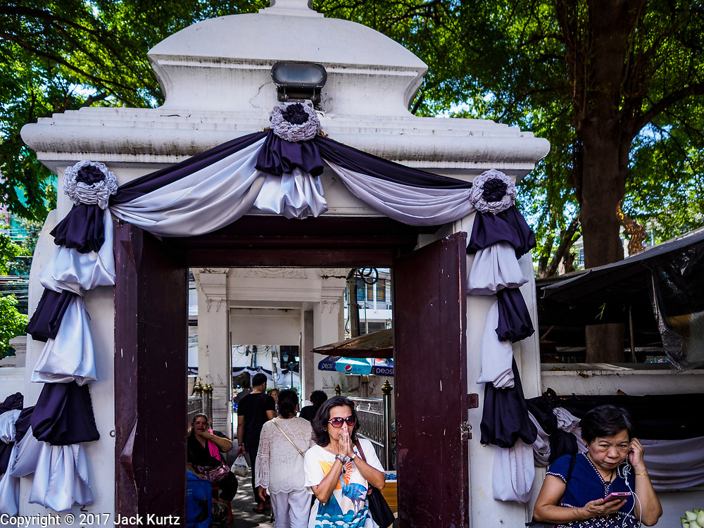 """11 APRIL 2017 - BANGKOK, THAILAND:  A woman bows as she enters Wat Chana Songkhram for a Songkran merit making service. Songkran is the traditional Thai Lunar New Year. It is celebrated, under different names, in Thailand, Myanmar, Laos, Cambodia and some parts of Vietnam and China. In most places the holiday is marked by water throwing and water fights and it is sometimes called the """"water festival."""" This year's Songkran celebration in Thailand will be more subdued than usual because Thais are still mourning the October 2016 death of their revered Late King, Bhumibol Adulyadej. Songkran is officially a three day holiday, April 13-15, but is frequently celebrated for a full week. Thais start traveling back to their home provinces over the weekend; busses and trains going out of town have been packed.    PHOTO BY JACK KURTZ"""