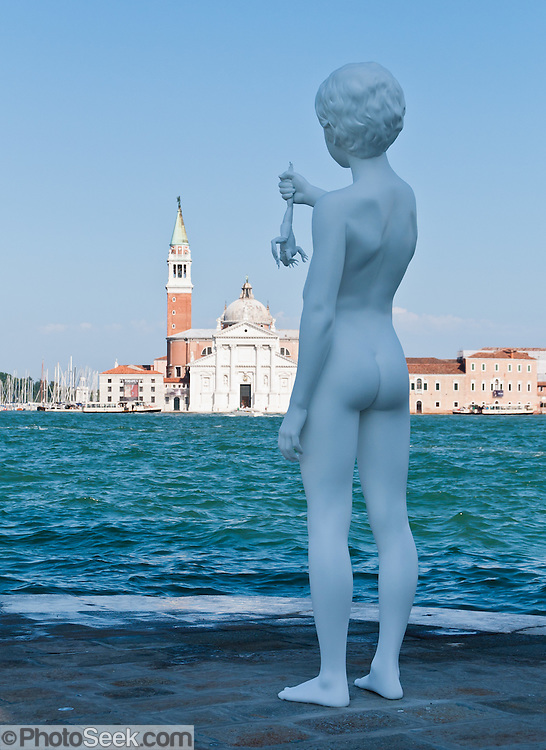 """In 2009, American sculptor Charles Ray (born 1953) installed """"Boy with Frog"""" at the Punta della Dogana on Giudecca island, sestiere of Dorsoduro, Venice, Italy, Europe. The white eight-foot-tall sculpture depicts a boy holding a large frog above Giudecca Canal. Across the lagoon is Chiesa di San Giorgio Maggiore, a 16th century Benedictine church on the island of the same name. The basilica was designed in the classical renaissance style by Andrea Palladio and built from 1566-1610. The campanile (bell tower), first built in 1467, fell in 1774, and was rebuilt in neo-classic style by 1791. Venice (Venezia) is the capital of Italy's Veneto region, named for the ancient Veneti people from the 10th century BC. The romantic """"City of Canals"""" stretches across 117 small islands in the marshy Venetian Lagoon along the Adriatic Sea Europe."""