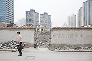 "An area of low-rise housing is demolished for development. The writing on the wall reads, ""Overusage of Electricity Prohibited"". Shanghai, China, 2007"