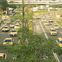 Taxi's in ofrmation on a Taipei road.