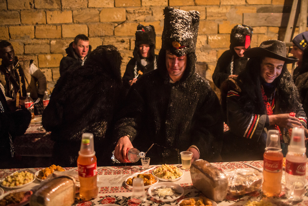 Revelers in costume take a break from their celebrations of the Malanka Festival to eat lunch, and pour a shot of samogon, a home-made vodka, on Thursday, January 14, 2016 in Krasnoilsk, Ukraine. The annual celebrations, which consist of costumed villagers going in a group from house to house singing, playing music, and performing skits, began the previous sundown, went all night, and will last until evening.