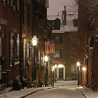 Romantic Boston winter photography of old colonial brick row houses along Acorn Street on a beautiful winter evening. Acorn Street near Louisburg Square is one of the most prestigious address in Beacon Hill. Street lanterns provide the warm night light in Beacon Hill. Acorn Street, often mentioned as the most frequently photographed street in the United States of America. It is a narrow lane paved with cobblestones that was home to coachmen employed by families in Mt. Vernon and Chestnut Street mansions.<br />