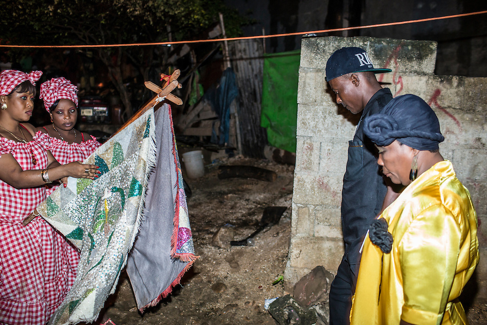Members of the Societe Ti Pilon Baka vodou troupe, at right, are greeted by members of another troupe at an annual nighttime ceremony on Sunday, December 14, 2014 in Leogane, Haiti. The city of Leogane, about 20 miles west of Port-au-Prince, was the closest city to the epicenter of the 2010 earthquake, and damage there was extensive.