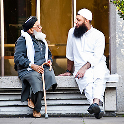 London, UK - 21 July 2012: two Muslim faithful sit and talk at the Ramadan Iftar 2012 celebrations hosted at the Islamic Cultural Centre (ICC) in Regents Park.