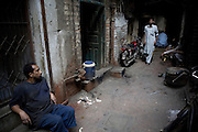 Workers wait for power to be restored at a workshop in the 'Old City' sector of Lahore. ..Parts of Pakistan are reportedly suffering 12-20-hours of electricity load shedding (power outages) per day. One for the reasons given by the government is that of illegal tampering of electrical meters and bribery of meter readers...Many industries are suffering as a result of not being ale to use production machinery during load shedding and are unable meet deadlines for manufacture and delivery of goods.