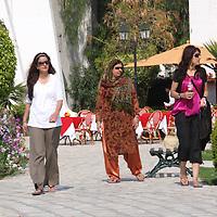 Scenes from Tunisia's resort area, El Kantouai, three women in a mix of styles