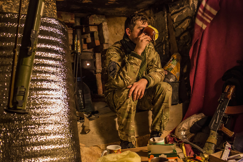 "PERVOMAISKE, UKRAINE - NOVEMBER 17, 2014: ""Patrick,"" member of the 5th platoon of the Dnipro-1 brigade, a pro-Ukraine militia, who chose not to give his name because he is from a nearby town and fears for the safety of his family, drinks tea inside a bunker where he sleeps at their post underneath a bridge in Pervomaiske, Ukraine. CREDIT: Brendan Hoffman for The New York Times"