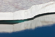 A large sheet of ice is reflected in Frozen Lake, located in the Sunrise area of Mount Rainier National Park, Washington. While the lake surface thaws in the summer, it's usually surrounded by large packs of snow and ice year-round. The lake serves as the water supply for the Sunrise area of the park.