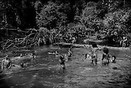 Batek Negrito children swimming and eating little white berries that grow in bushes that line the river on the part of their territory that borders Taman Negara National Park and hence has not been clear-cut, like the rest of their ancestral homeland.  Near Kuala Koh, Kelantan, Malaysia.