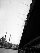 Fishing lines dropped from the Galata Bridge, with Yeni Mosque in the background