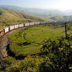 An eastbound BNSF intermodal train heads uphill around a big curve in the Tehachapi Mountains.