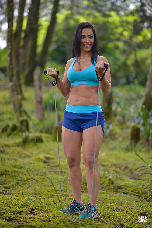 Hispanic woman in her forties exercising fitness workout with resistance bands in a forest.