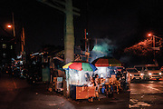 Jessica Concepcion, 15, serves fried peanuts from a food cart at an intersection near the University of The Philippines in Quezon City in Metro Manila, Philippines on Saturday night. The third year high school student works at the food cart every day until 1 a.m., then is at school by 7 a.m.