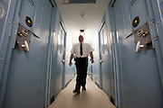 A male prison officer walks down the corridor of one of the residential wings. HMP Send, closed female prison. Ripley, Surrey.