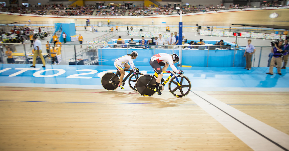 Kate O'Brien (R) of Canada defeats Juliana Gaviria Rendon of Colombia in the third race of the women's cycling Sprint Semifinals to advance to the gold medal race Sunday night against Canadian teammate Monique Sullivan at the 2015 Pan American Games in Toronto, Canada, July 19,  2015.  AFP PHOTO/GEOFF ROBINS