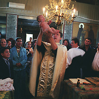 Relatives of the Badea and Bratu families gather in the Romanian Orthodox Church to observe the baptism of Sarion Bratu Badea, by Priest Christian Baroianu. In the Romanian Orthodox Church , near the Roma camp of SIntesti, near Bucharest..