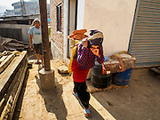 02 MARCH 2017 - SANKHU, NEPAL: Laborers carry bricks to a home being rebuilt in Sankhu. Each basket weighs about 80 pounds. Almost all of the work is being done by hand. There is more construction and rebuilding going on in Sankhu, west of central Kathmandu, than in many other parts of the Kathmandu Valley nearly two years after the earthquake of 25 April 2015 that devastated Nepal. In some villages in the Kathmandu valley workers are working by hand to remove ruble and dig out destroyed buildings. About 9,000 people were killed and another 22,000 injured by the earthquake. The epicenter of the earthquake was east of the Gorka district.   PHOTO BY JACK KURTZ