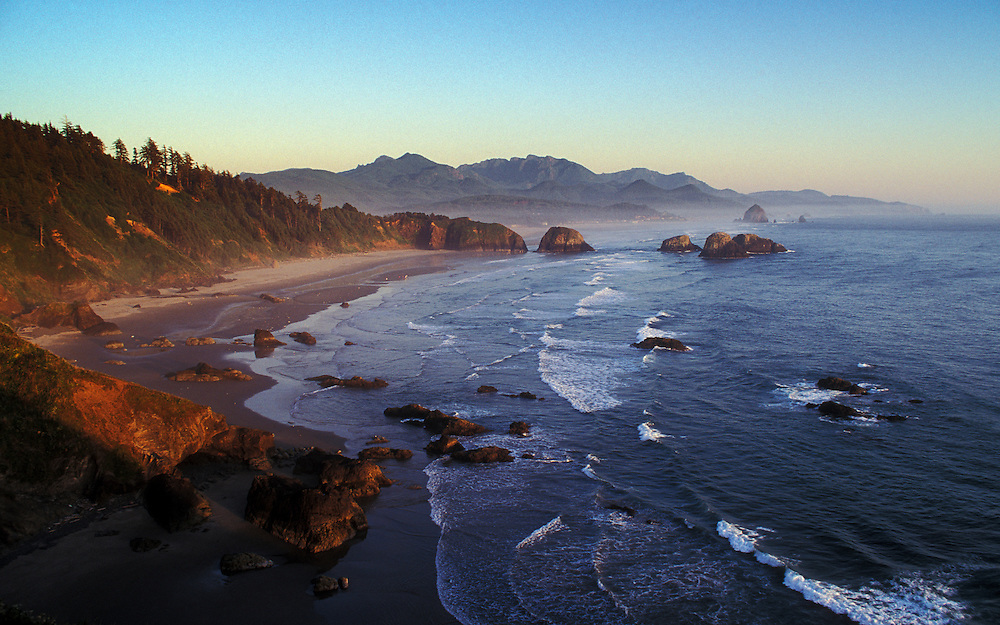 View of Crescent Beach, Cannon Beach, Haystack Rock and coast to Hug Point from Ecola State Park at sunset; Oregon.