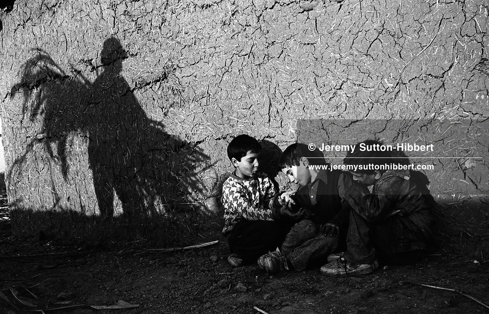 Nicolae Veriga Stanescu works into the evening as children from his family play beside a hut, in the Kalderash Roma camp of Sintesti, near Bucharest.