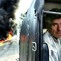 "A man waits in the back of a truck where the road has been blocked by an oil pipeline set on fire by rebels of the Revolutionary Armed Forces of Colombia, FARC, on the road leading to La Hormiga, in the southern Putumayo state. As part of a U.S. backed counter narcotics offensive, Colombian government troops have fumigated an estimated 62,000 acres of coca fields in Putumayo. Despite predictions that the fumigation campaign would cause rebels and paramilitaries, who earn huge profits by ""taxing"" the cocaine industry, to drift away, rebels clash almost daily with government soldiers and the paramilitary forces. (Photo/Scott Dalton)"