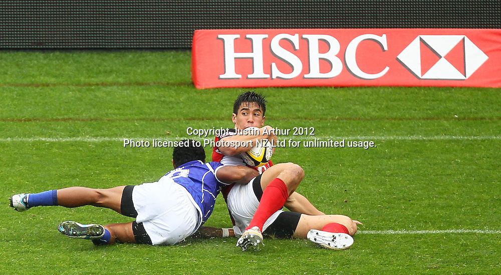 Canada's Sean Duke looks for support as Samoa's Tom Iosefo makes the tackle. Hertz Wellington Sevens - Day two at Westpac Stadium, Wellington, New Zealand on Saturday, 4 February 2012. Photo: Justin Arthur / photosport.co.nz