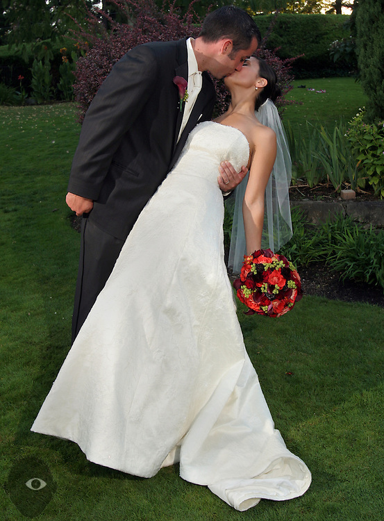 The newly married couple share a dramatic kiss as group shots continue.