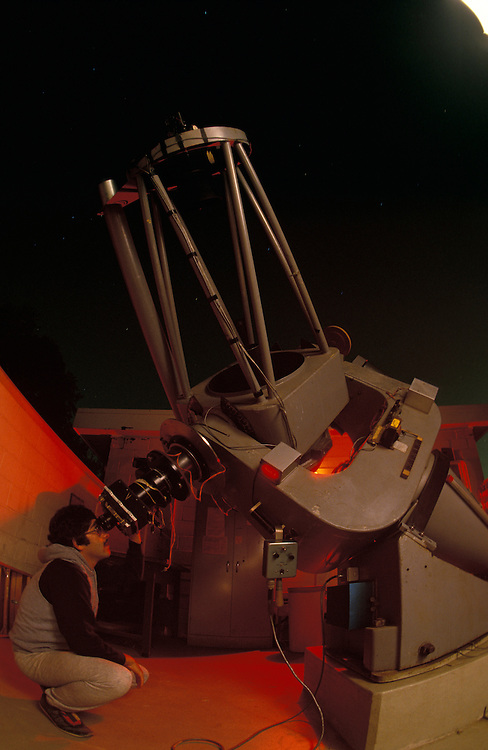 USA, Maryland, College Park, Astronomy student peers through telescope at University of Maryland