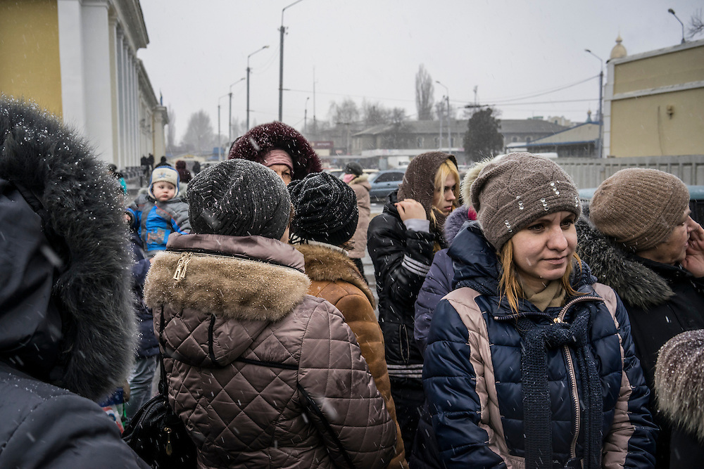 People displaced by fighting between pro-Russia rebels and Ukrainian forces in Eastern Ukraine wait outside a tent to receive free second-hand clothes at a processing center for internally displaced people located at the train station on Monday, February 9, 2015 in Slovyansk, Ukraine.