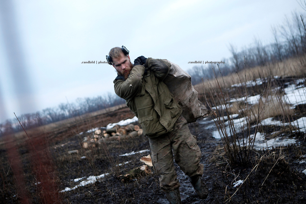 Craig carries a bag full of wet firewood from backwards their trench to the position at donetsk frontline.<br />
