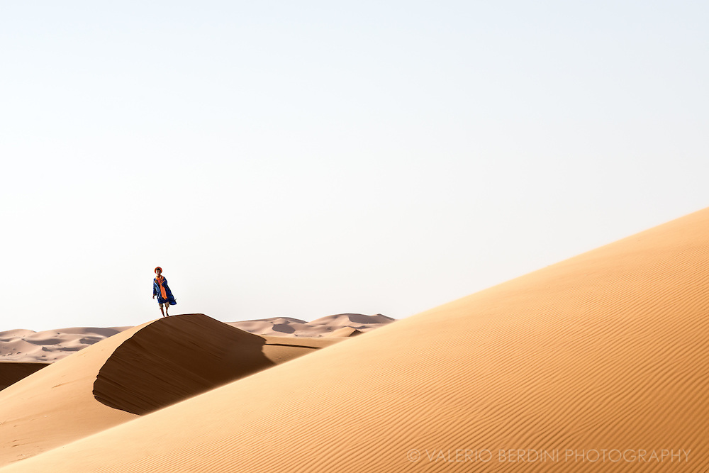 """A young berber guide walks on the edge of a sand dune of the Sahara desert in Merzouga in Morocco. """"Where are the people?"""" resumed the little prince at last. """"It's a little lonely in the desert…"""" """"It is lonely when you're among people, too,"""" said the snake."""""""