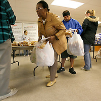 LEHIGH ACRES, FL -- January 23, 2009 -- Marie Sallade of Lehigh Acres bags up free bread at the bread line at Faith Lutheran Church in Lehigh Acres, Fla., on Friday, January 23, 2009.  Lehigh Acres has become a symbol for the fallen American Dream - with only two years separating itself from housing market boomtown to a current landscape of abandoned developments and struggling businesses.