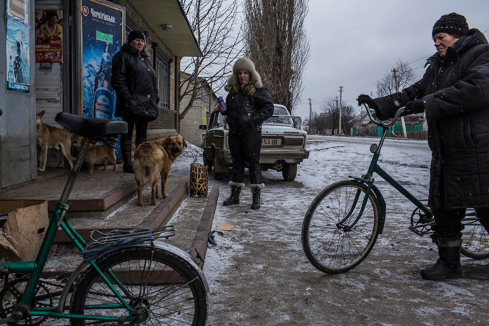 DEBALTSEVE, UKRAINE - FEBRUARY 7, 2015: People stand outside a shop in Debaltseve, Ukraine. The Ukrainian-controlled town, surrounded on three sides by rebel forces, has been undergoing heavy shelling for more than a week, but a brief ceasefire allowed many residents to evacuate and others to simply venture out from their homes. CREDIT: Brendan Hoffman for The New York Times