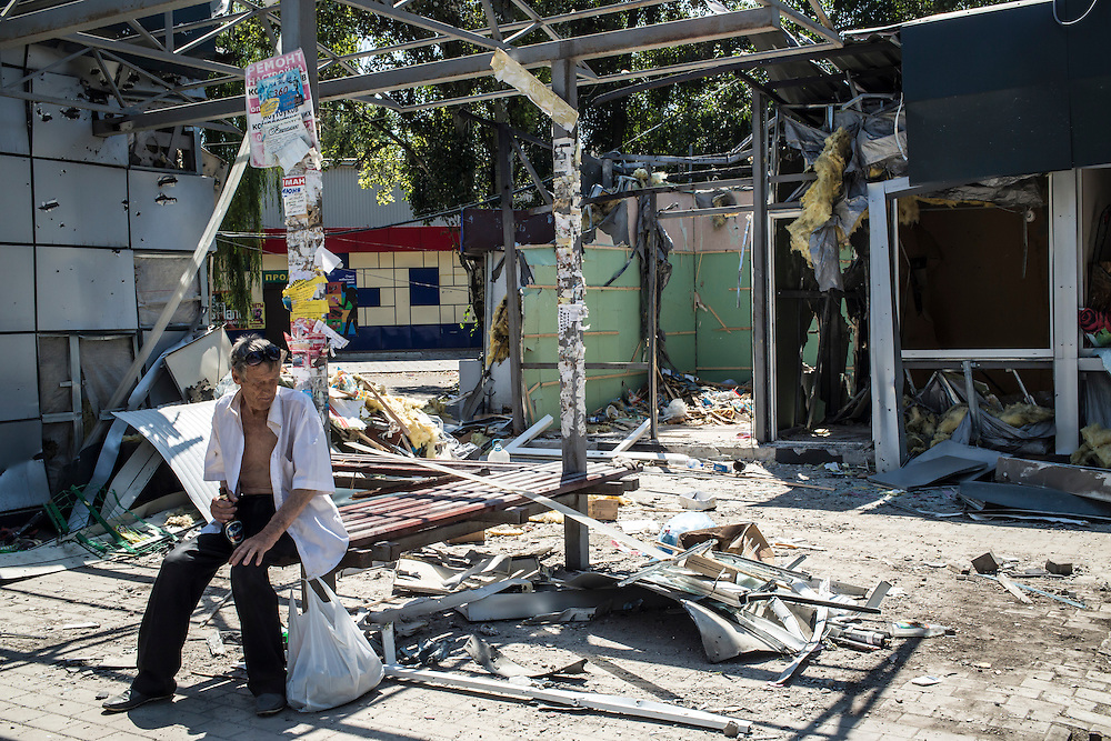 A man sits on a bench amid damage from the shelling of shops in the Oktyabrskaya neighborhood on Sunday, July 27, 2014 in Donetsk, Ukraine.