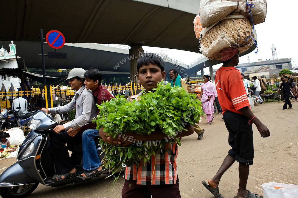 A young boy, about the same age and in the same area where Shafiq Syed worked more than 20 years ago, is carrying vegetables on the streets surrounding the Bangalore City Market, Karnataka, India. Shafiq, now 34, used to sleep and make a meagre living here when he escaped various times from his father's home at the tender age of 11 to live as a street child in Bangalore first, and then in Mumbai. It was during the time living next to Churchgate train station, in central Mumbai, that he was selected to become the main character for the cast of Cannes' Camera D'Or 1988 winner Salaam Bombay. After the movie he failed to become a star, fell back into poverty and lived on the streets for years before he moved on to become a rickshaw (tuk-tuk) driver in his home city of Bangalore, Karnataka State, India.
