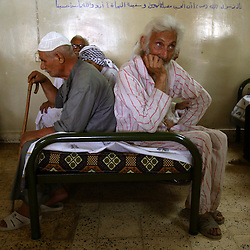 Najim Al Deen Najef, 70, on the right, waits to be seen by a South Korean humanitarian organization at a retirement home in Sadr City, Baghdad, Iraq, July 22, 2003. Even though most families in Iraq care for their aging relatives at home, there is still a need for the facility, which is the largest of its kind in Baghdad housing 45 women and 87 men. The facility was not looted during the war, but it is still lacks some funding and is in need of medications for patients with chronic conditions such as heart disease and diabetes.
