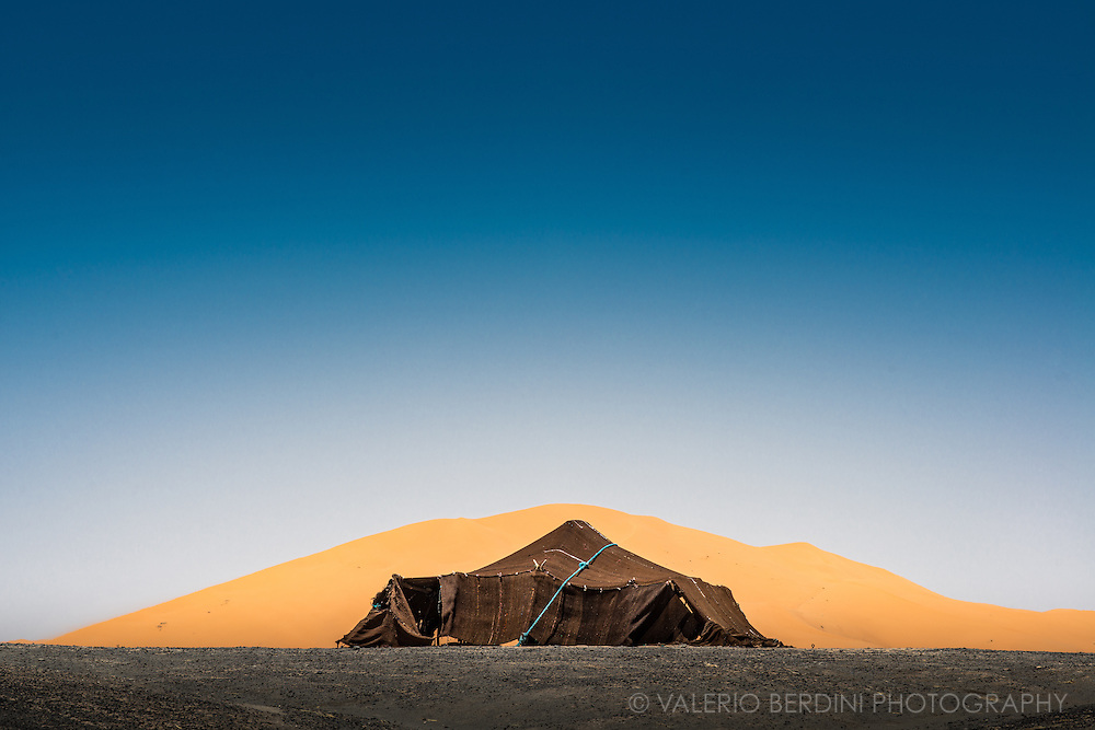"""A berber tent put up in the black desert in front of one of the giant sand dunes of Erg Chebby, near Merzouga in the Moroccan Sahara at the border with Algeria on May 2015. Berbers call """"black desert"""" the darker volcanic ground to differentiate it from the sandy dunes."""