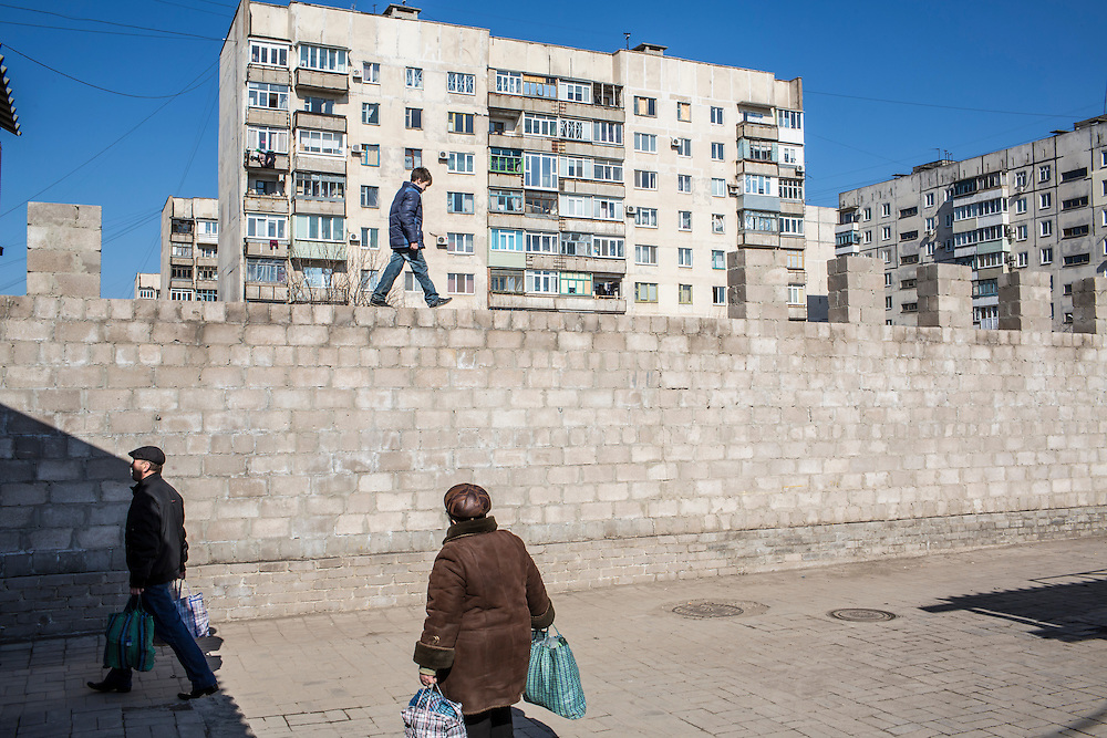 Boys play atop a wall at the Kievsky Market, which on January 24 suffered a direct hit by a number of Grad rockets, on Sunday, March 8, 2015 in Mariupol, Ukraine. Photo by Brendan Hoffman, Freelance