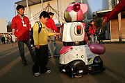Kid playing with ALSOK guard robot while it is patroling at the AICHI WORLD EXPO 2005, Nagoya 5-April-2005, Japan