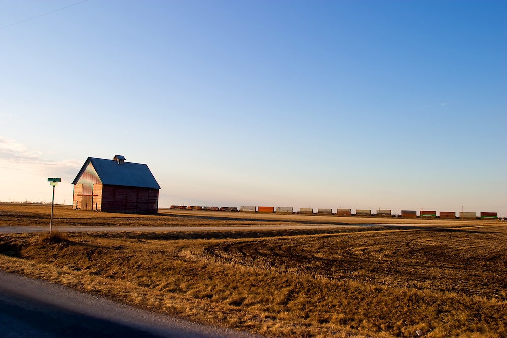 A train of international ocean containers speeds across the flat plains of central Illinois, passing an old barn in a rural area near Streator, IL.
