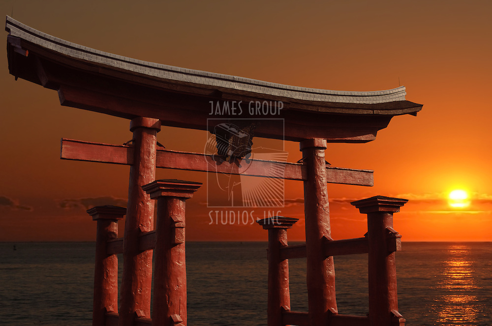 Traditional floating Japanese gate at the entry to a Shinto shrine called a torii with a red setting sun in the background