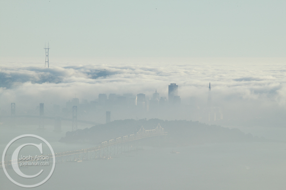 Downtown San Francisco, California and the Bay Bridge stand out against a summer fog bank.