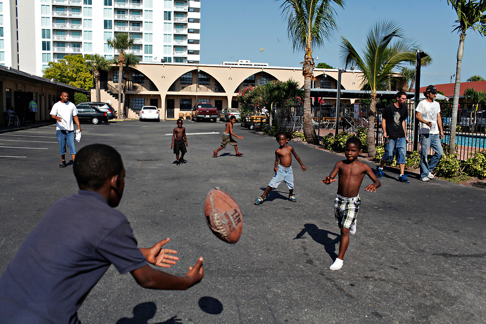 MELISSA LYTTLE | Times<br /> An afternoon pick-up game of 3-on-3 football takes over the parking lot at the Mosley Motel.