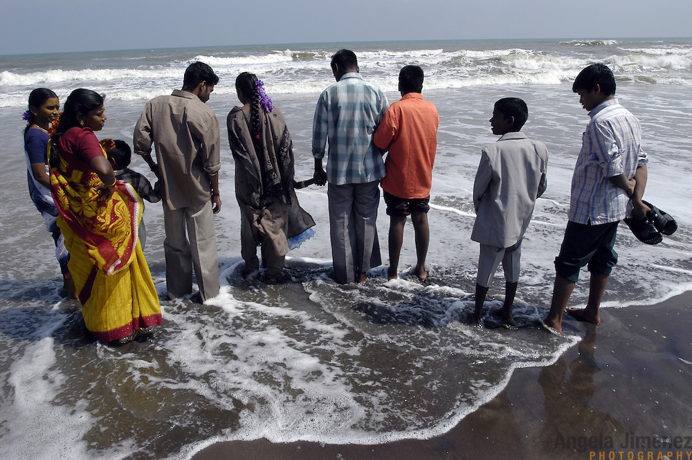 A well-off family on a tourist visit from the inland town of Mayiladurei wades in the ocean in Chinnangudi, a fishing village in Tamil Nadu, India, on January 16, 2005, after the area was struck by the Indian Ocean Tsunami on December 26, 2004, killing 40 of the villagers and destroying nearly all of the village's fishing equipment. Generated by an earthquake on the ocean floor, the tsunami devastated the fishing industry along the southeastern coast of India.